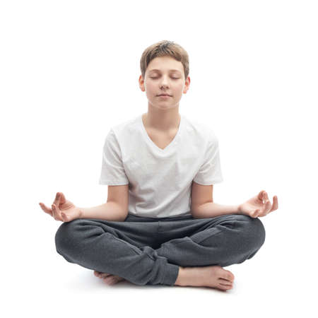 childen: Meditating caucasian 12 years old childen boy in a white t-shirt, composition isolated over the white background