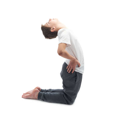 childen: Caucasian 12 years old childen boy in a white t-shirt stretching or doing yoga. Composition isolated over the white background