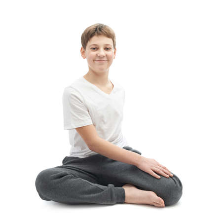 Caucasian 12 years old childen boy in a white t-shirt stretching or doing yoga. Composition isolated over the white background