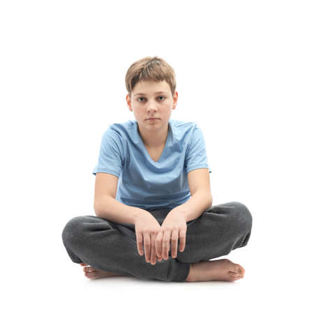 full shot: Tired caucasian 12 years old childen boy in a blue t-shirt sitting in a lotus position, full shot composition isolated over the white background Stock Photo