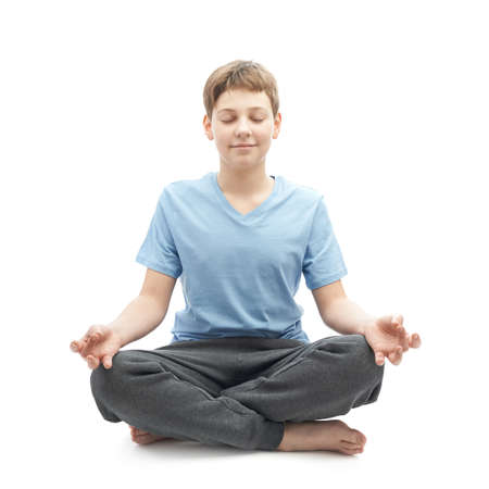 childen: Full shot of a caucasian 12 years old childen boy in a blue t-shirt doing yoga or stretches. Composition isolated over the white background