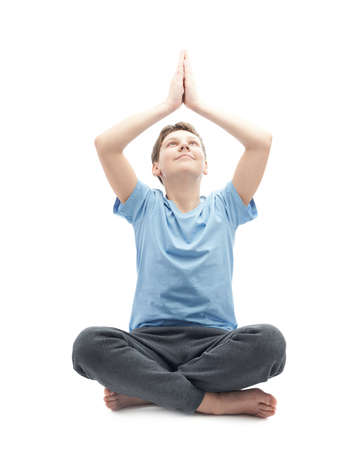 full shot: Full shot of a caucasian 12 years old childen boy in a blue t-shirt doing yoga or stretches. Composition isolated over the white background