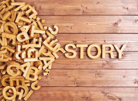 story: Word story made with block wooden letters next to a pile of other letters over the wooden board surface composition Stock Photo