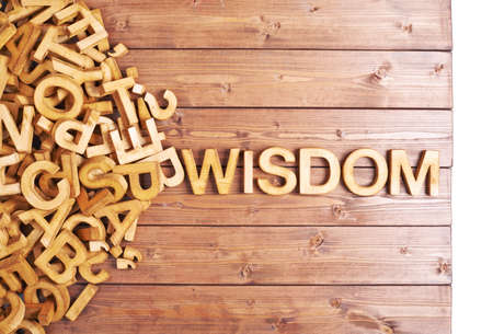 Word wisdom made with block wooden letters next to a pile of other letters over the wooden board surface composition photo