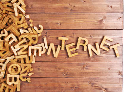Word internet made with block wooden letters next to a pile of other letters over the wooden board surface composition photo