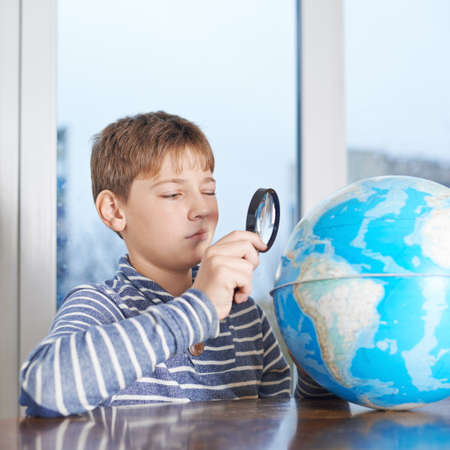 schoolkid search: 12 years old children boy sitting at the wooden desk looking at the earth globe through the magnifying glass, composition against the window