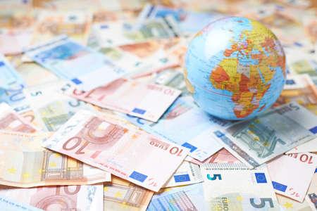 Tiny Earth wereldbol over het oppervlak bedekt met de meervoudige bankbiljet rekeningen Stockfoto