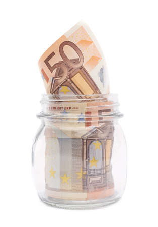 Multiple fifty euro bank notes in a glass jar isolated over the white background photo