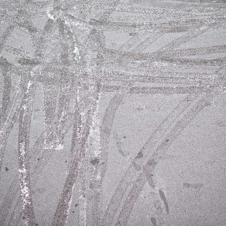 Frosted asphalt covered with the tire tracks as a background composition photo