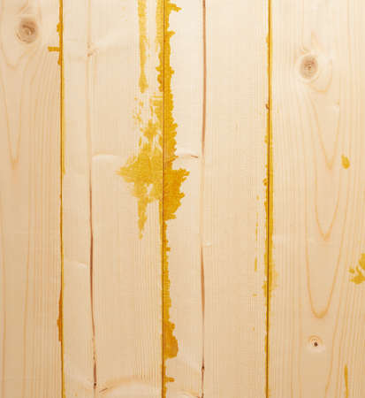 multiple stains: Surface covered with multiple pine wood boards with the paint stains and leaks in the gaps, as an abstract background composition