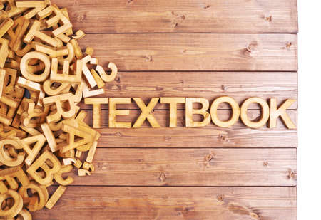 Word textbook made with block wooden letters next to a pile of other letters over the wooden board surface composition photo