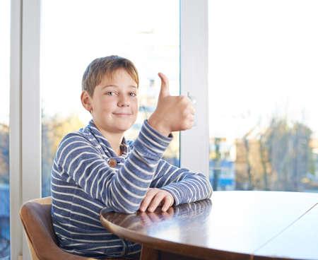 Feliz 12 años chico childen sentado en el escritorio de madera que muestra un pulgar hacia arriba gesto, composición contra la ventana Foto de archivo