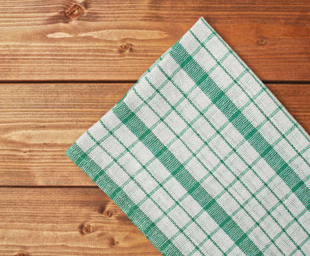 Green tablecloth or towel over the surface of a brown wooden table Stock Photo