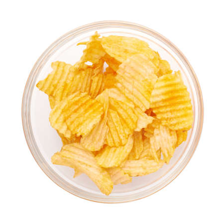 party food: Multiple yellow potato chips snacks in a glass bowl, composition isolated over the white background, top view above foreshortening