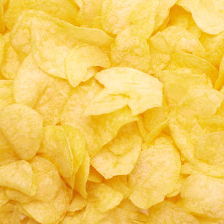 unhealthful: Surface covered with yellow wavy potato chips snacks as a background composition