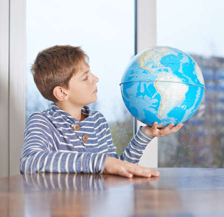 childen: Surprised 12 years old childen boy sitting at the wooden desk while holding the Earth globe and looking at it, composition against the window