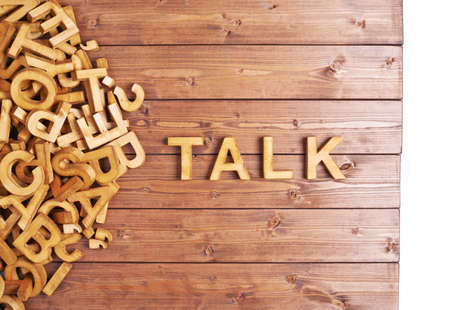 Word talk made with block wooden letters next to a pile of other letters over the wooden board surface composition photo
