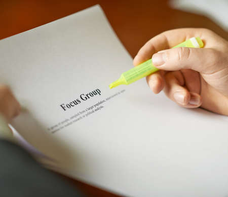 focus group: Focus group definition as a shallow depth of field close-up composition of a man in a business suit working with the text