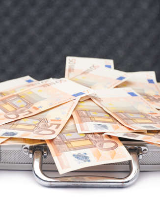 Suitcase full of fifty euro bank note bills isolated over the white background photo