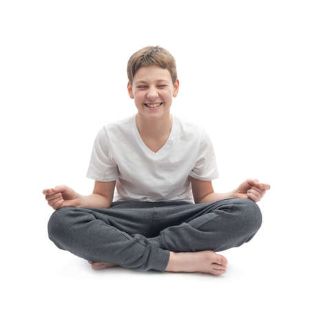 smiling buddha: Meditating caucasian 12 years old children boy in a white t-shirt, composition isolated over the white background