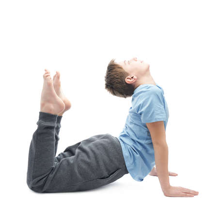 Full shot of a caucasian 12 years old children boy in a blue t-shirt doing yoga or stretches. Composition isolated over the white background Stock Photo