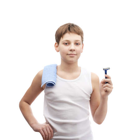 shaving blade: Happy young boy in a sleeveless white shirt with a towel over his shoulder and and a shaving razor blade in his hand, composition isolated over the white background