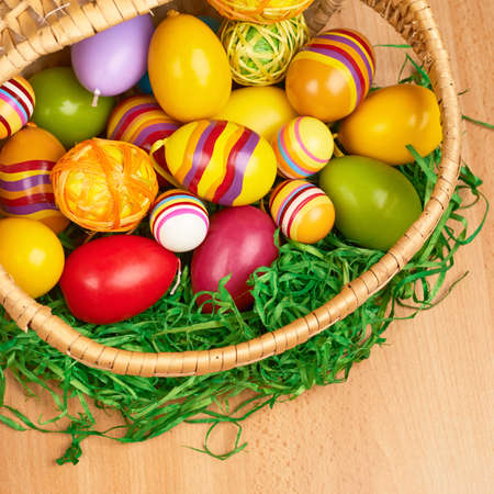 Basket full of colorful Easter eggs over the wooden surface, top view photo