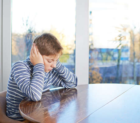 childen: Sad 12 years old childen boy sitting at the wooden desk with his hand covering ears, composition against the window Stock Photo