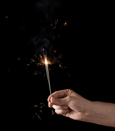 lowkey: Holding a burning sparkler, low-key composition isolated over the black background