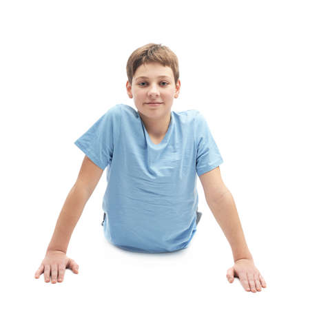 full shot: Full shot of a caucasian 12 years old children boy in a blue t-shirt doing yoga or stretches. Composition isolated over the white background Stock Photo