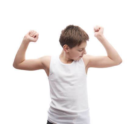 Happy young boy in a sleeveless white shirt looking at his biceps muscles, composition isolated over the white background