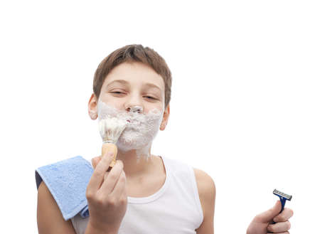 face covered: Happy young boy in a sleeveless white shirt with his face covered with the shaving foam, ready to shave, composition isolated over the white background Stock Photo