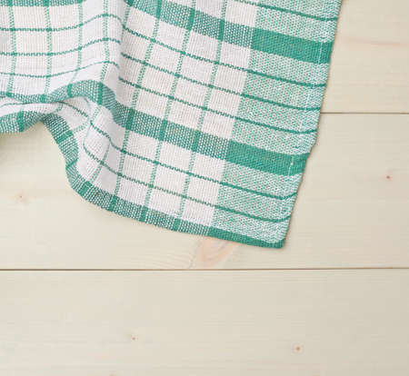 table surface: Green squared tablecloth or towel over the surface of a wooden table Stock Photo