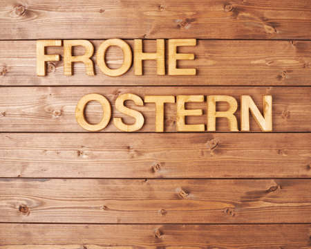 Ostern: Words Frohe Ostern as Happy Easter in german language made of wooden letters as a festive Easter background composition