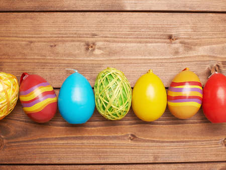 ing: Colorful Easter eggs decoration lying ing line over the brown wooden surface as a copyspace festive background composition