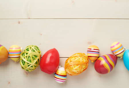 ing: Colorful Easter eggs decoration lying ing line over the wooden surface as a copyspace festive background composition