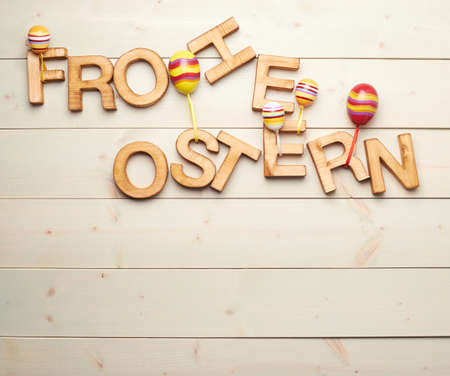 Ostern: Words Frohe Ostern as Happy Easter in german language made of wooden letters decorated with colorful toy eggs as a festive Easter background composition