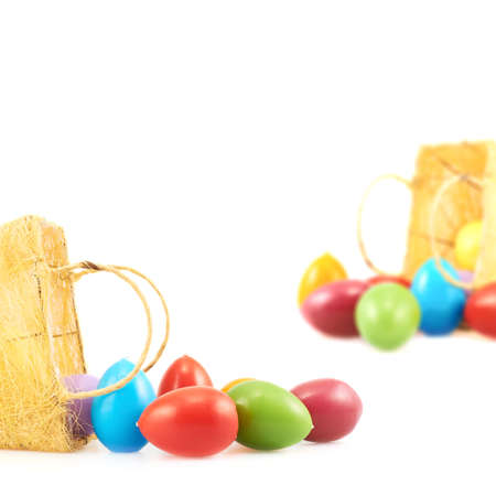 falling out: Egg candles falling out of the basket over the white background as a copyspace Easter composition