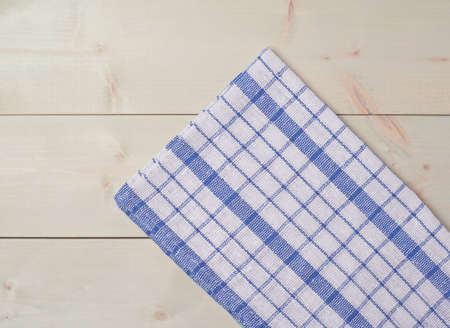 table surface: Blue squared tablecloth or towel over the surface of a wooden table