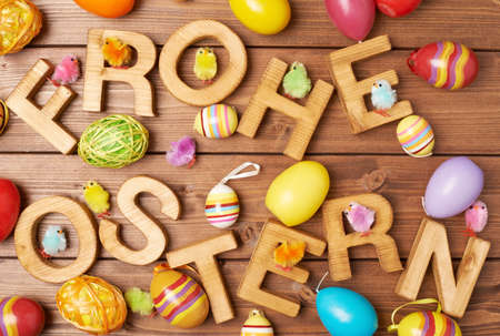 Ostern: Words Frohe Ostern as Happy Easter in german language made of wooden letters and surrounded with multiple egg decorations as a festive Easter background composition