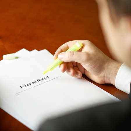 balanced budget: Balanced budget definition as a shallow depth of field close-up composition of a man in a business suit working with the text