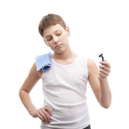 shaving blade: Young boy in a sleeveless white shirt with a towel over his shoulder and and a shaving razor blade in his hand, composition isolated over the white background