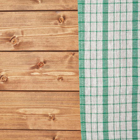 table surface: Green tablecloth or towel over the surface of a brown wooden table Stock Photo