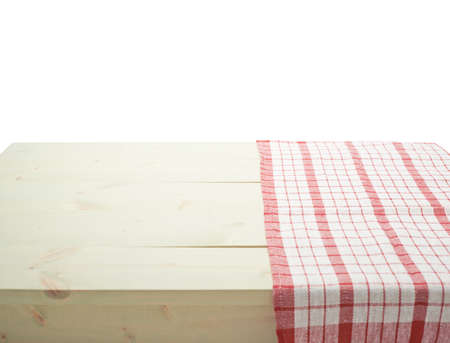 Red tablecloth or towel over the surface of a wooden table, composition isolated over the white background Standard-Bild