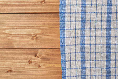 Blue tablecloth or towel over the surface of a brown wooden table photo