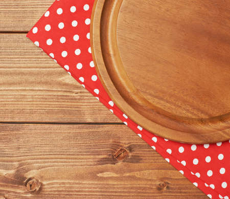table surface: Red polka dot tablecloth or towel over the surface of a brown wooden table with a round wooden tray on top of it