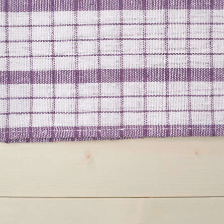 squared: Violet squared tablecloth or towel over the surface of a wooden table Stock Photo