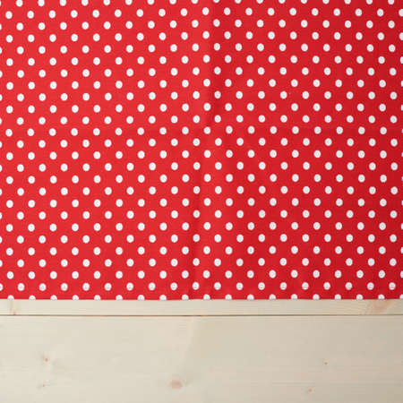 dot surface: Red polka dot tablecloth or towel over the surface of a wooden table Stock Photo