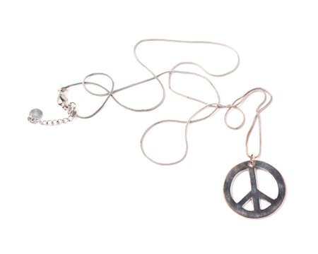 antiwar: Worn metal peace sign necklace isolated over the white