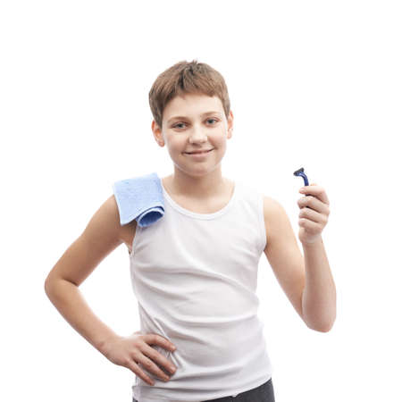 shaving blade: Happy young boy in a sleeveless white shirt with a towel over his shoulder and and a shaving razor blade in his hand, composition isolated over the white